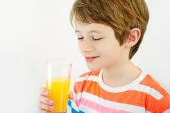 Suco de laranja da bebida do menino com uma palha foto de stock