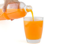 Suco de laranja derramado da garrafa a um vidro Fotografia de Stock Royalty Free