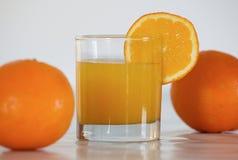 Suco de laranja e duas laranjas Foto de Stock Royalty Free