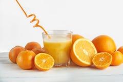 Suco de laranja e laranjas recentemente espremidos Imagem de Stock Royalty Free