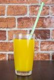 Suco de laranja em um copo com um tubo em uma tabela de madeira e em um fundo da parede de tijolo Imagem de Stock Royalty Free