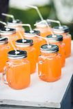 Suco de laranja em umas latas com palhas Imagem de Stock