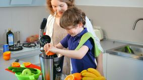 Suco de laranja fresco caseiro caucasiano novo da mãe e da criança na cozinha com Juicer bonde video estoque