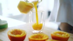 Suco de laranja fresco de derramamento do frasco de vidro no vidro Peças alaranjadas espremidas filme