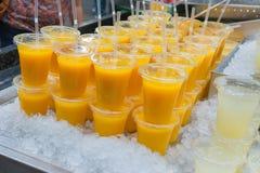 Suco de laranja fresco em vidros plásticos em uma cama do gelo Fotografia de Stock Royalty Free