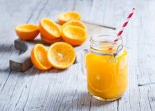 Suco de laranja sobre dentro do frasco com as sobras dos shell em seu lado Foto de Stock Royalty Free