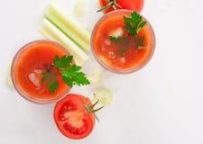 Suco de tomate com aipo no fundo branco Fotografia de Stock Royalty Free