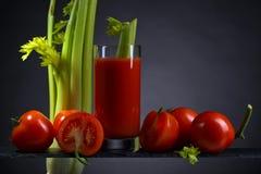 Suco de tomate com tomates e varas de aipo Fotografia de Stock Royalty Free