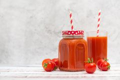 Suco de tomate fresco nos vidros e nos tomates de cereja no fundo claro Com espaço da cópia foto de stock