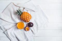 Suco do abacaxi e de fruto da paixão no fundo branco da tabela fotos de stock