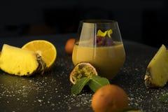 Suco do batido do cocktail de fruto em um vidro transparente na tabela, nas laranjas e nas tangerinas com abacaxi e paixão fotos de stock