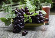 Suco do fruto e de uva em um vidro na tabela fotografia de stock