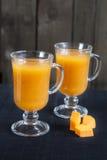 Suco fresco da abóbora no vidro alto, partes de abóbora fresca na mesa preta Imagens de Stock Royalty Free
