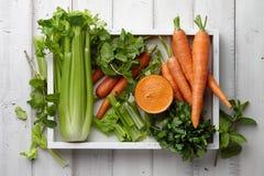 Suco fresco da cenoura e do aipo na bandeja de madeira Imagens de Stock