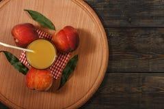 Suco fresco do pêssego com pêssegos frescos em um fundo escuro Vista superior, espaço da cópia Comer saudável Suco fresco com pês Fotografia de Stock Royalty Free