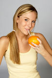 Suco sorvendo da mulher loura da laranja Imagens de Stock