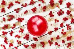 Suco vermelho recentemente espremido com cubos de gelo e grupos de corintos vermelhos em uma tabela de madeira branca com pintura Foto de Stock