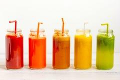 Sucos frescos da desintoxicação de vidro em umas garrafas da fileira no fundo branco imagens de stock
