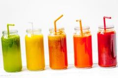 Sucos frescos da desintoxicação de vidro em umas garrafas da fileira no fundo branco fotos de stock