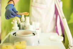 Sucrage dans un salon de beauté mains dans la spatule bleue de prise de gants avec de la cire pour le dépilage de la boîte images libres de droits