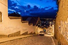 SUCRE BOLIVIA - APRIL 21, 2015: Nattsikt av en brant gata i Sucre, Boliv royaltyfria foton