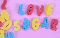 Sucre d'amour de mots sur la table rose Images stock