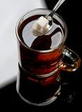 Sucre de morceau dans le thé Photographie stock