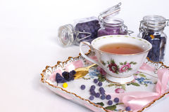 Sucre des fleurs d'une violette avec une tasse de thé Images stock