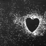 Sucre en poudre en forme de coeur sur le fond en bois noir Photographie stock