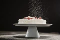 Sucre en poudre tombant au-dessus du gâteau blanc sur le support Images libres de droits