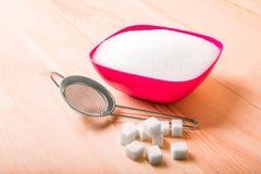 Sucre glacé dans le plat rose sur une table brune sur un fond blanc Un petit tamis et les cubes de sucre blanc sont sur une table Photos stock