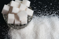 Sucre granulé et sucre raffiné de blanc sur un fond noir image libre de droits