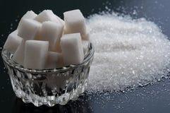 Sucre raffiné et sucre granulé sur la surface noire image libre de droits