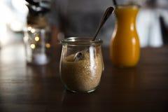 Sucre roux en pot en verre et jus frais orange sur la table en bois photo libre de droits