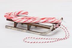 Sucrerie Cane On Wooden Sledge de Noël blanc photographie stock libre de droits