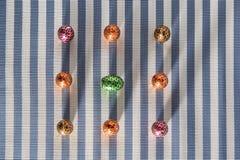 Sucrerie colorée de bonbons sur le fond rayé Oeufs de dessert de chocolat - tradition heureuse de Pâques images stock
