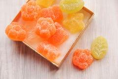 Sucrerie colorée de gelée dans la boîte actuelle d'or Table en bois blanche À Images libres de droits