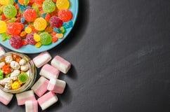 Sucrerie colorée lumineuse, sucrerie, guimauve, bonbons sur un fond foncé de plat bleu Image stock