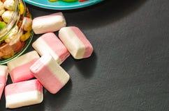 Sucrerie colorée lumineuse, sucrerie, guimauve, bonbons sur un fond foncé de plat bleu Image libre de droits