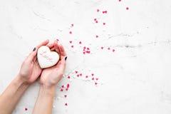 Sucrerie de jour du ` s de Valentine Biscuit en forme de coeur avec amour de lettrage dans des mains sur l'espace gris-clair de v Photo libre de droits