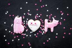 Sucrerie de jour du ` s de Valentine Biscuit en forme de coeur avec amour de lettrage et minou sur la vue supérieure de fond noir Photos libres de droits