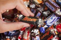 Sucrerie de Mars chez la main de la femme Images stock