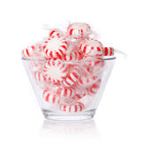 Sucrerie de menthe poivrée dans le bol en verre sur le blanc. Sucrerie en bon état rayée rouge de Noël Image stock