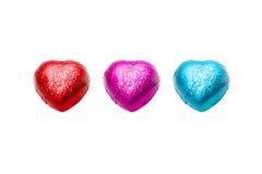 Sucrerie de trois de couleur coeurs de chocolat sur le fond blanc Images stock