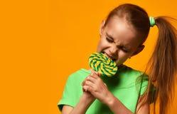 Sucrerie douce de lollypop de jeune de petit enfant de fille morsure heureuse d'enfant Photographie stock