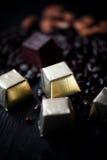 Sucrerie en aluminium, amandes et graines de tournesol d'or en chocolat se trouvant sur un fond foncé studio photo stock