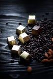 Sucrerie en aluminium, amandes et graines de tournesol d'or en chocolat se trouvant sur un fond foncé studio photos stock