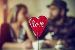 Sucrerie en forme de coeur avec des couples à un arrière-plan Photo stock