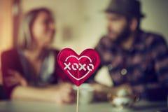 Sucrerie en forme de coeur avec des couples à un arrière-plan Photos stock