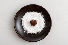 Sucrerie en forme de coeur de chocolat d'un plat brun avec la poudre de sucre sur le fond en bois Photo libre de droits